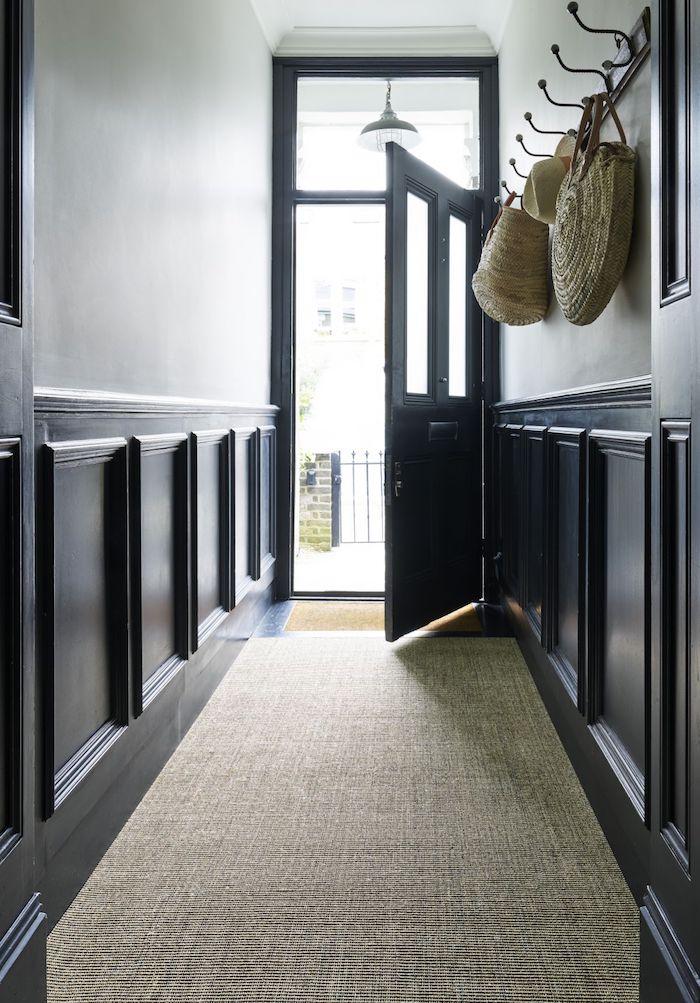 aménagement couloir soubassement bois repeint de noir et porte noire tapis gris et peinture murale blanche