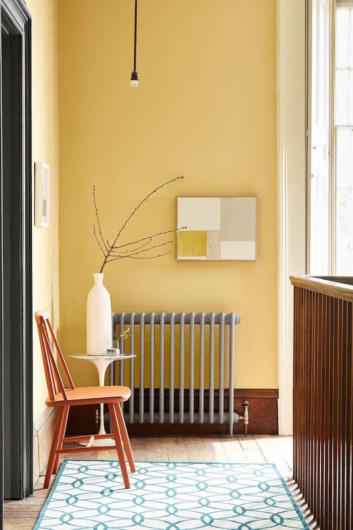 aménagement coulour sur palier avec radiateur gris chaise bois murs jaunes tapis géométrique sur parquet bois brut