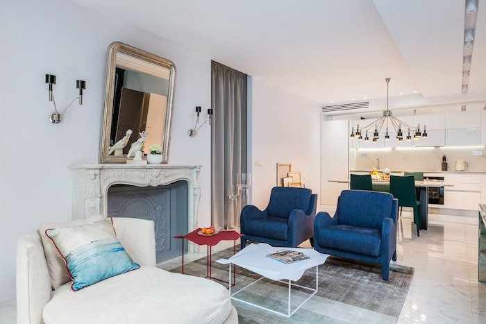 aménagement cuisine ouverte sur salon chaises vertes fauteuils bleus tapis gris cheminée blanche fauteuil blanc suspensioin à plusieurs lumières