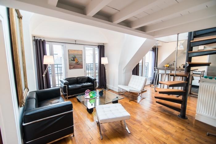 aménagement studio avec mezzanine fauteuils cuir noirs table de verre cuisine blanche sous pente parquet bois clair et ecalier roulant