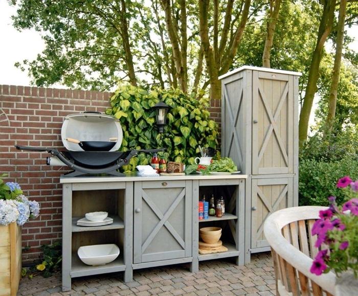 amenagement cuisine exterieur mur briques cagette bois cache pot arbuste fleurie chaise bois meuble jardin armoires bois gris peinture
