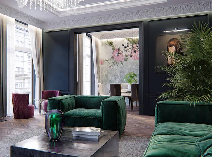 appartement deco parisienne avec canapé et fauteuil vert rubin tapis gris fauteuils bordeaux parquet chevron ouverture sur salle à manger design