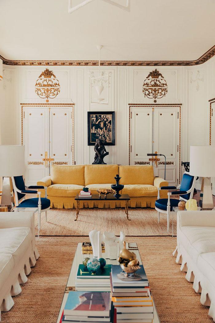 appartement design decoration canapé jaune tapis beige chaises blanc et bleu canapés blancs murs blancs et déco murale à accents dorés