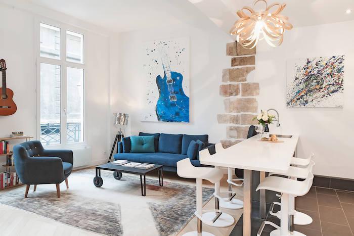 bar blanc entouré de chaises blanches tapis coloré table basse noire design canapé bleu tableau d art abstrait étagère bibliothèque à livres basse