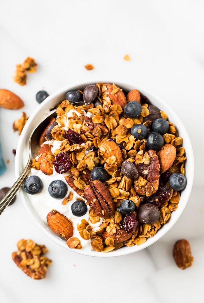 bol au yaourt pour petit dejeuner constituée de flocons d avoine amandes noix de pecan pepites de chocolat et fruits secs