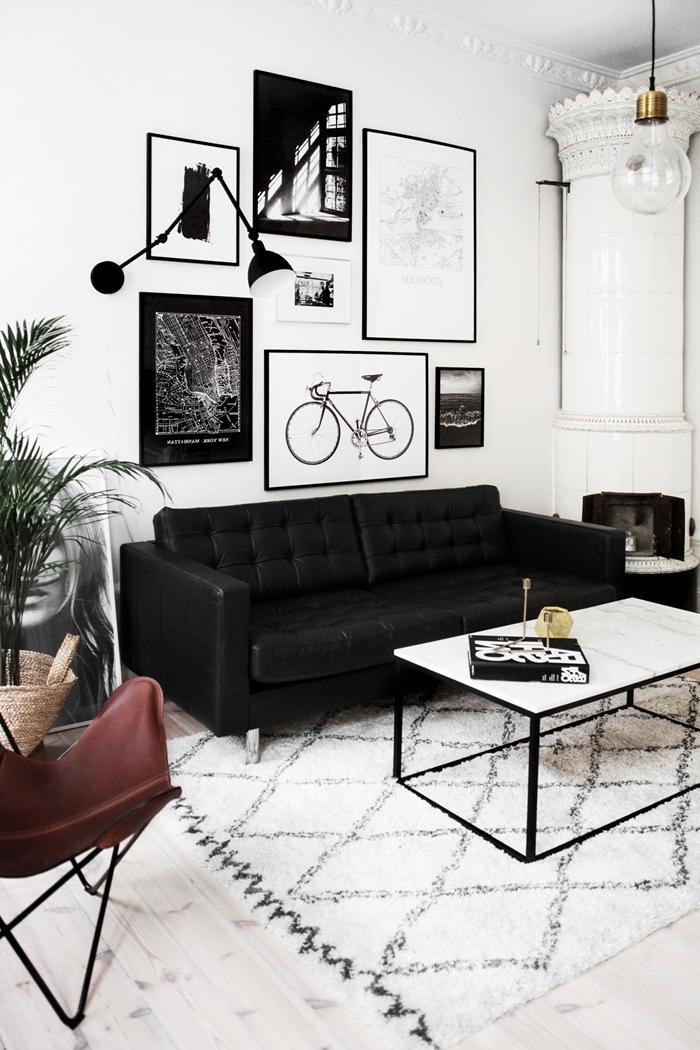 cadre noir et blanc décoration murale art mur cadres photos canapé noir tapis motifs géométriques blancs table basse blanc et noir