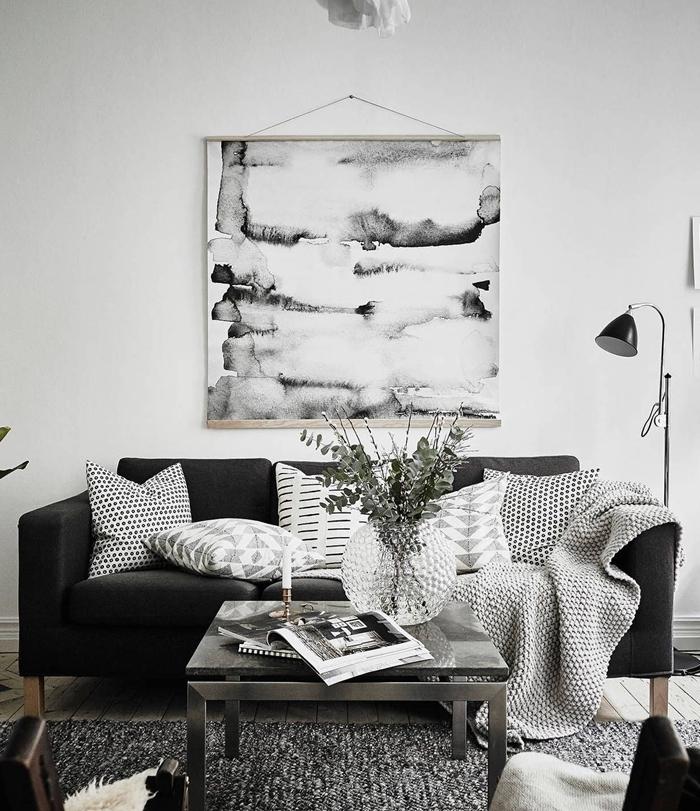 canapé noir tapis gris anthracite table salon basse métal plaid décoratifs coussins tableau noir et blanc lampe sur pied noir mat