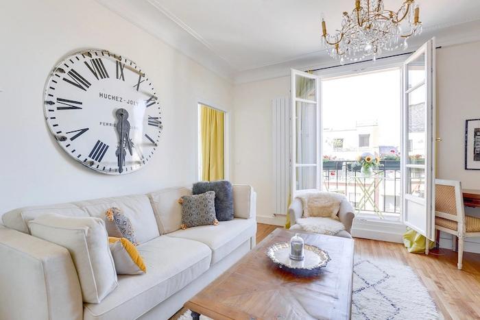 canapé blanc table basse bois design tapis blanc parquet bois clair murs blancs horloge vintage design idee de deco salon original style haussmannien