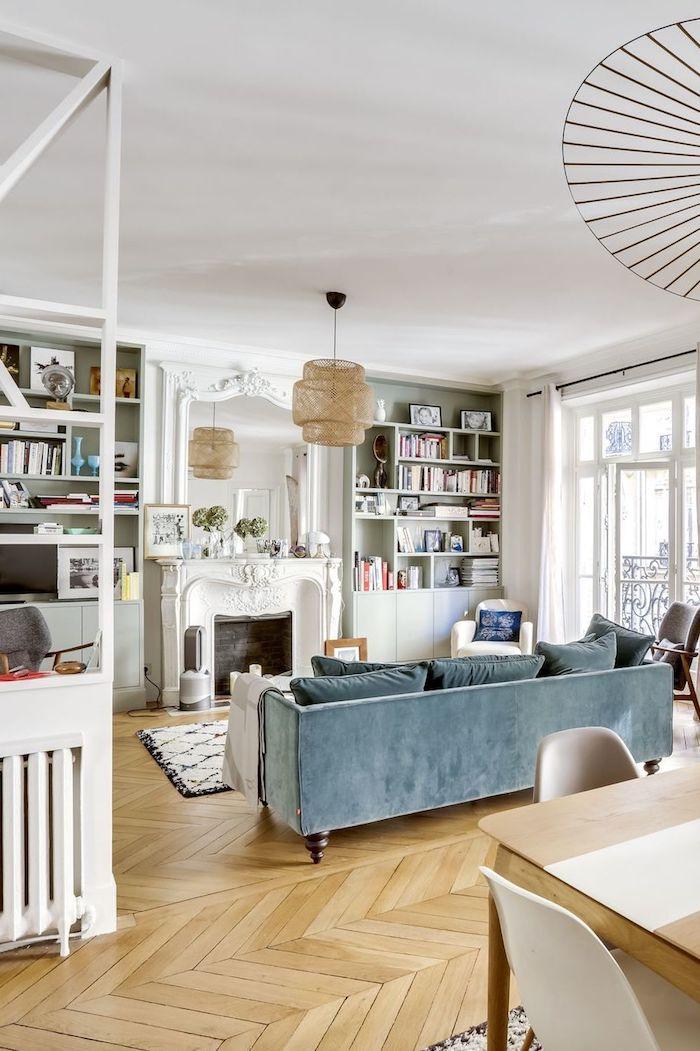 canapé bleu de gris parquet bois clair cheminée décprative meuble mural étagère blanche tapis noir et blanc