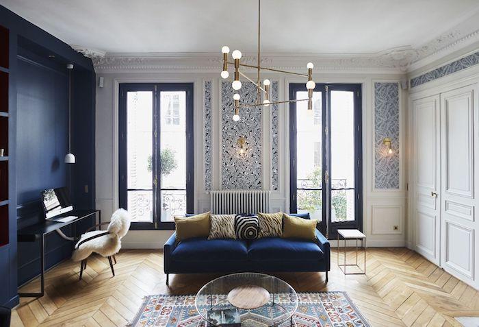 canapé bleu marine et mur bleu marine tapis coloré table basse verre coussins colorés et lés de papier peint décoratifs