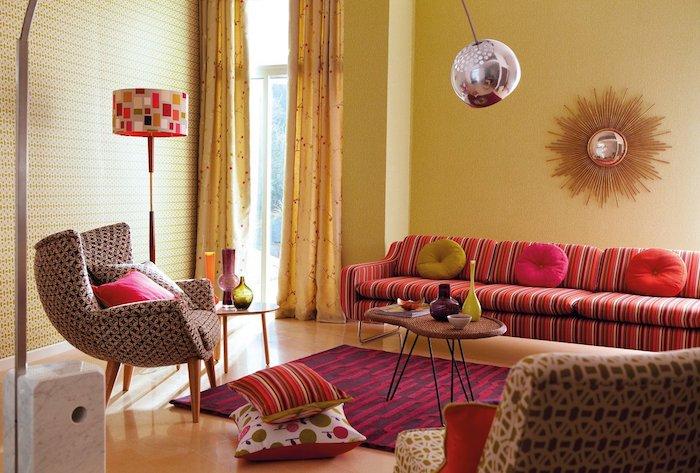 canapé coloré à ayures et papier peint geometrique tapis rouge et violet coussins colorés design année 70 vintage chic