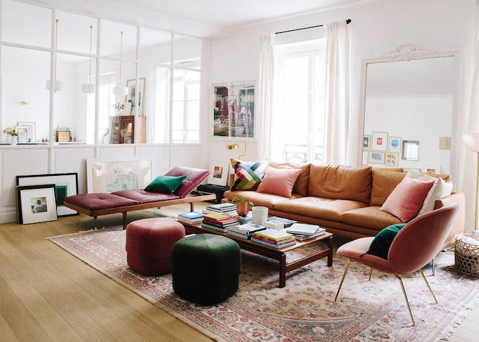 canapé en cuir marron table basse bois tabourets velours tapis oriental parquet bois murs blanchs décorés de tableaux d art