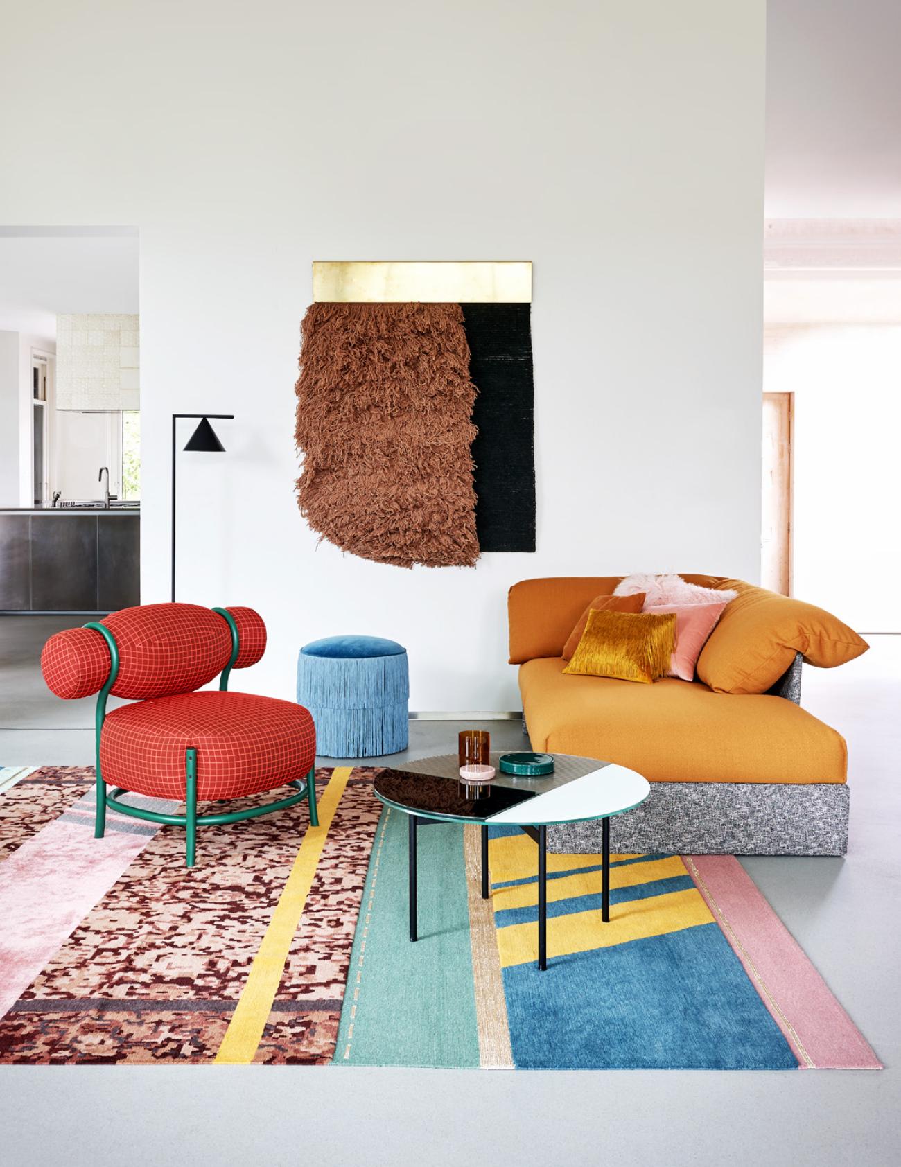 canapé jaune et gris clair fauteuil rouge et table basse metal et verre tapis coloré tissage mural sur mur blanc