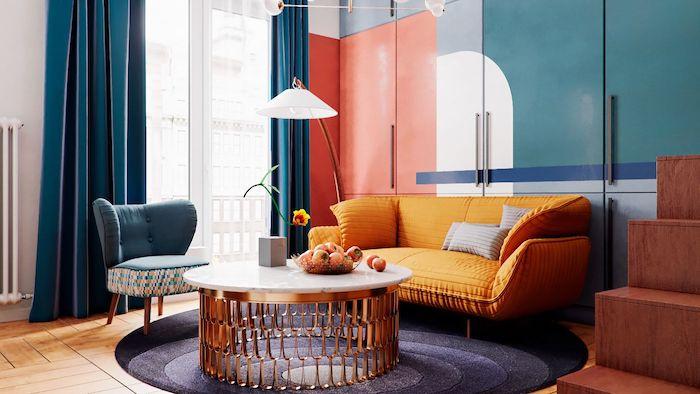 canapé jaune moutarde fauteuil bleu table basse marbre et laiton tapis rond gris rideaux bleus armoire bleu blanc et orangé parquet bois clair
