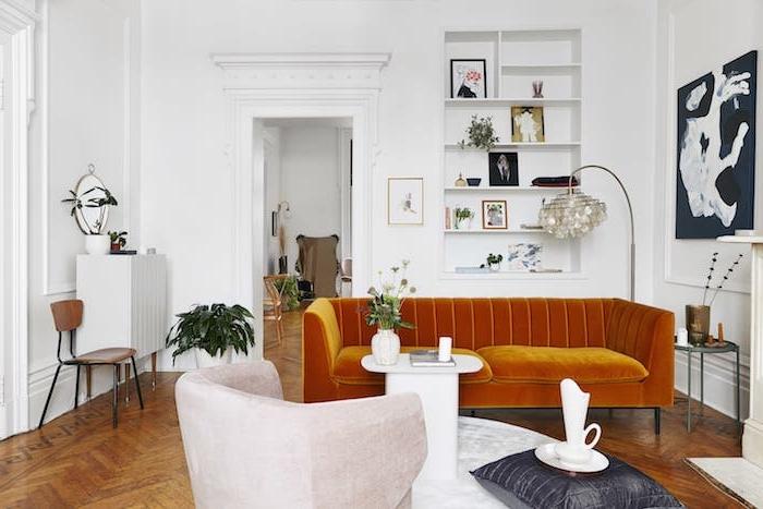 canapé jaune moutarde teinté de marron parquet bois brut chevron murs blanc décomurale tableaux d art table ronde marbre blanc