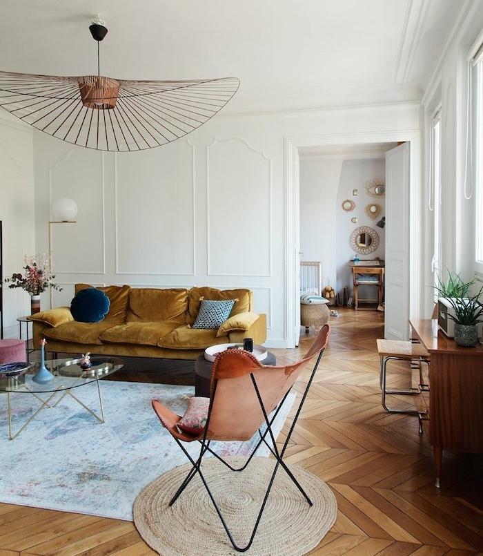 canapé jaune velours tapis bleuté table basse verre design chaise de cuir sur tapis rond parquet chevron clair