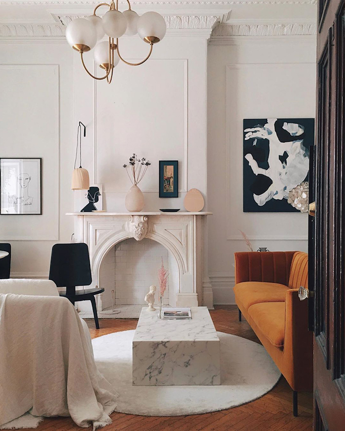 canapé marron clair teinté de jaune table basse en marbre cheminée décorative blanche murs décorés de cadres originaux parquet bois brut