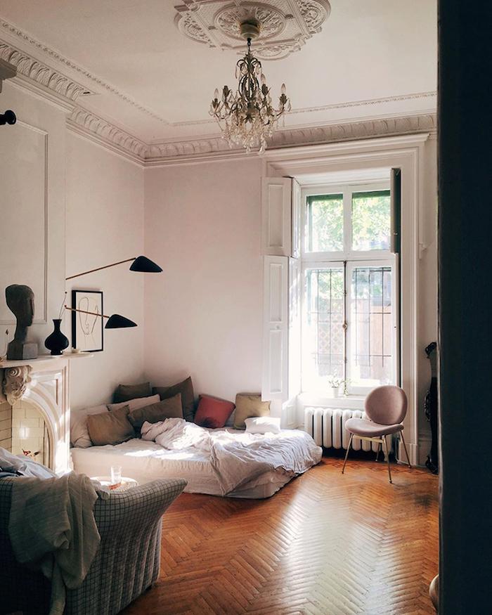 chambre à coucher dans interieur appartement parisien avec parquet chevron bois brut coussins colorés et matelas blanc murs blancs