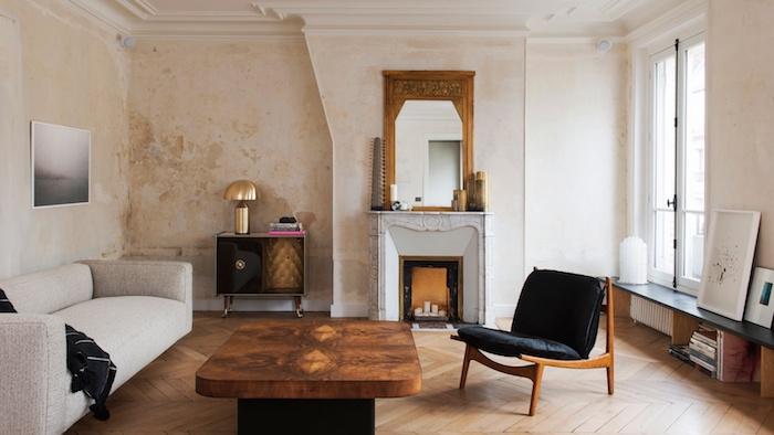 cheminée decorative desing minimaliste dans un appartement parisien de luxe avec canapé gris clair table basse plateau de bois et pied en metal mur effet rouille