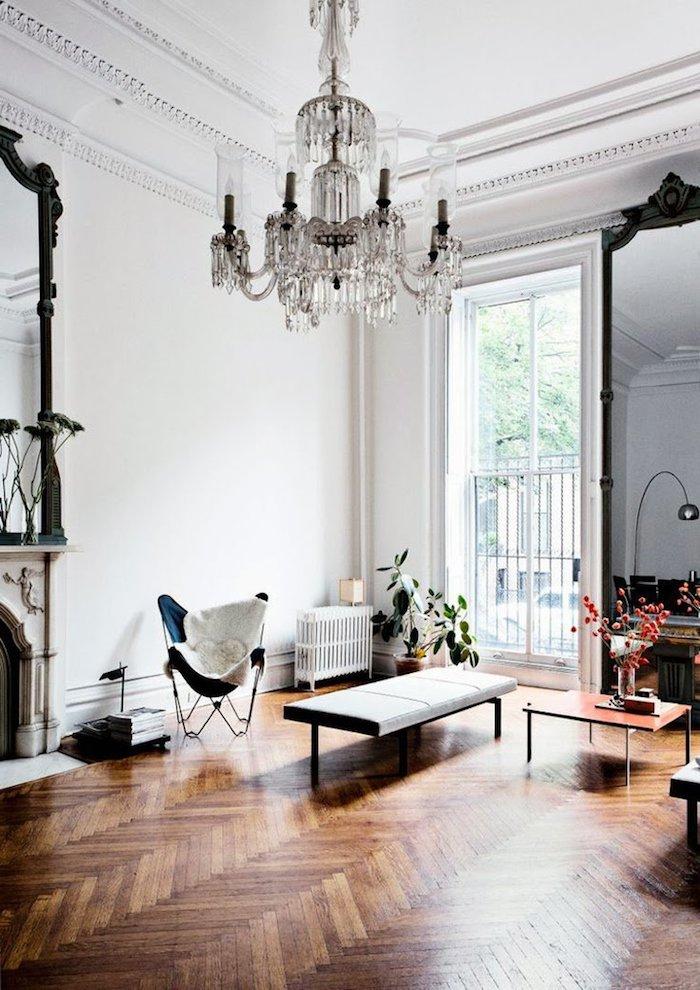 cheminée design parquet chevron table basse minimaliste fauteuil pliant bleu murs blancs plante verte d interieur