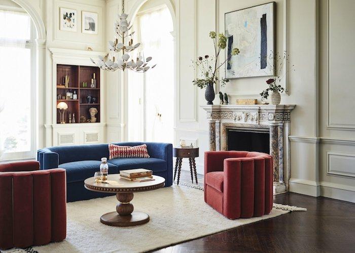 cheminée marbre fauteuil rouge forme arrondie canapé bleu table basse bois ronde tapis blanc murs blancs parquet marron foncé