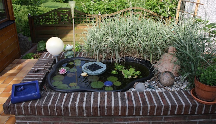 comment amenager un bassin japonais idee bassin préformé avec des nymphéas statuette bouddha gravier et plantes autour