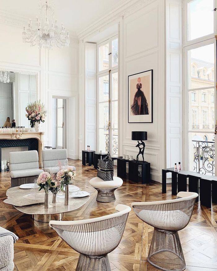 comment decorer un appartement parisien de luxe avec parquet bois fauteuils oeuf table desing metal accents meuble noir fausse cheminée décorative
