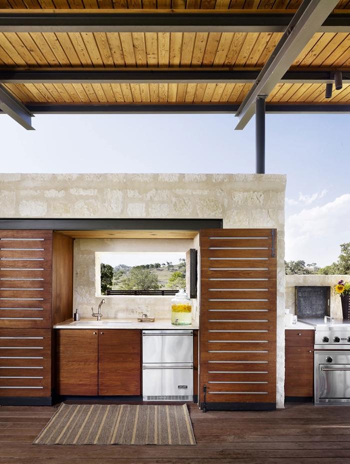 crédence fenêtre vue paysage nature aménagement cuisine extérieure couverte plafond toit bois meubles bas bois foncé