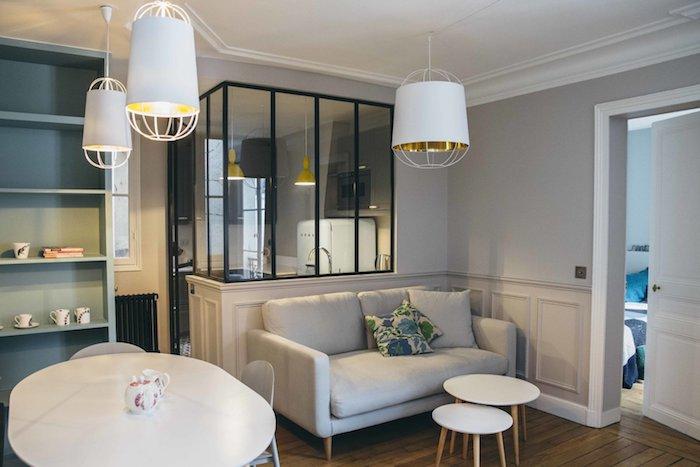 cuisine avec verrière industrielle séparée canapé gris tables blanches gigognes tables salle à manger blanche parquet bois chambre à coucher design à coté