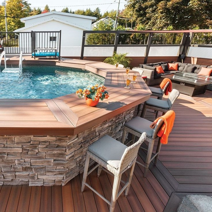 cuisine d été avec bar décoration cour arrière revêtement terrasse en bois chaises tressées extérieur bar bois pot fleur orange bouquet
