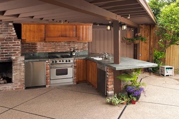 cuisine d été couverte agencement en l avec îlot crédence briques rouges déco campange style cuisine bois foncé et inox