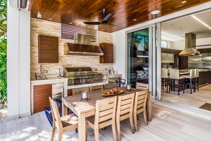 cuisine d été couverte aménagement extérieur ventilateur de plafond noir table à manger bois chaises extérieur cuisine inox et bois