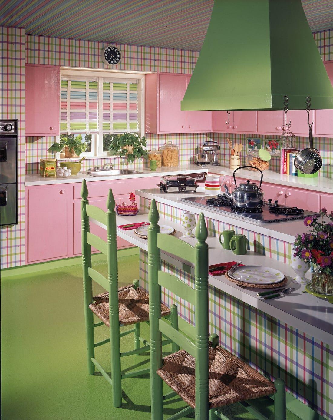 cuisine de couleur rose avec des meubles hauts et bas rose sol et chaises verts et ilot central à rayures