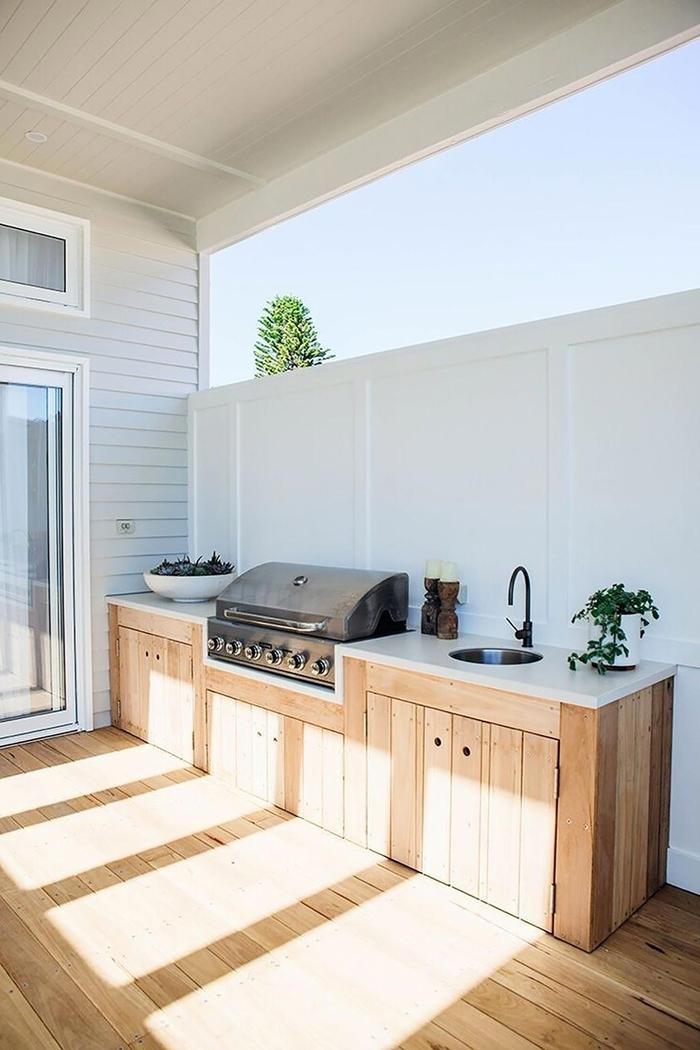 cuisine exterieure bois décoratin cuisine blanc et bois plan de travail blanc armoires bois clair poignées noires robinet noir