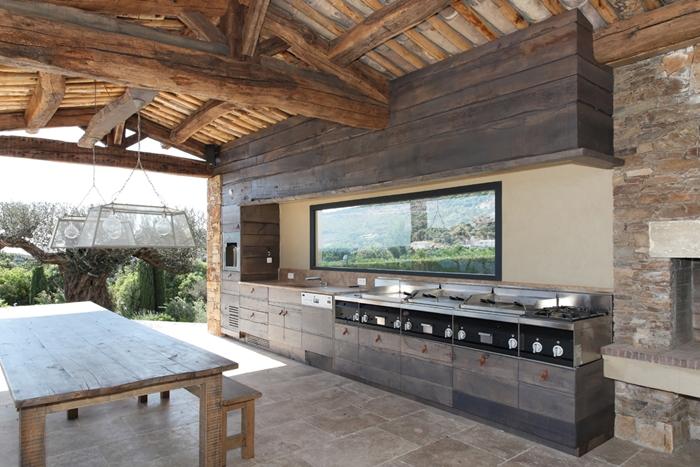 cuisine exterieure complete table à manger bois brut poutres bois apparentes plafond armoires bois gris crédence verre