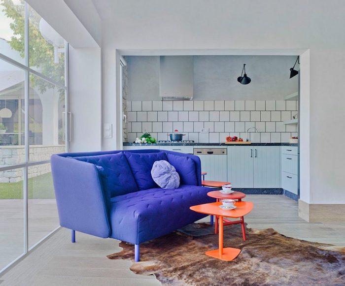 cuisne ouverte avec carrelage metro blanc sur salon avec tables basses oranges et canapé violet tapis fausse fourrure