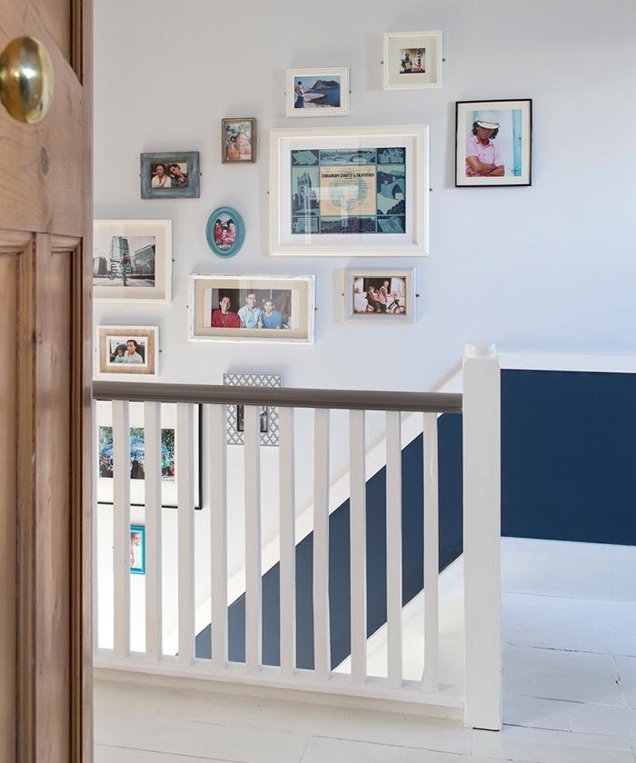 déco couloir mur bicolore soubassement bleu marine decoration murale interieur avec cadres photos blancs porte bois