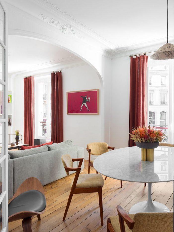 déco salon salle à manger ouverte avec canapé gris parquet bois clair table salle à manger marbre chaises bois rideaux rouges centre de table bouquet de fleurs