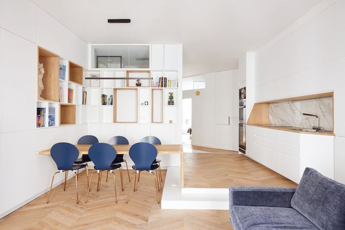 décoration appartement moderne avec parquet bois clair table bois et chaises bleues canapé gris credence marbre cuisine blanche et étagères blanches ouvertes dans meuble