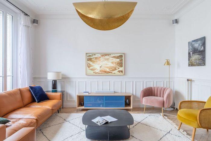 décoration salon appartement avec tapis blacn canapé de cuir marron faureuil jaune moutarde et rose poudré et table basse grise mur soubassement moulures