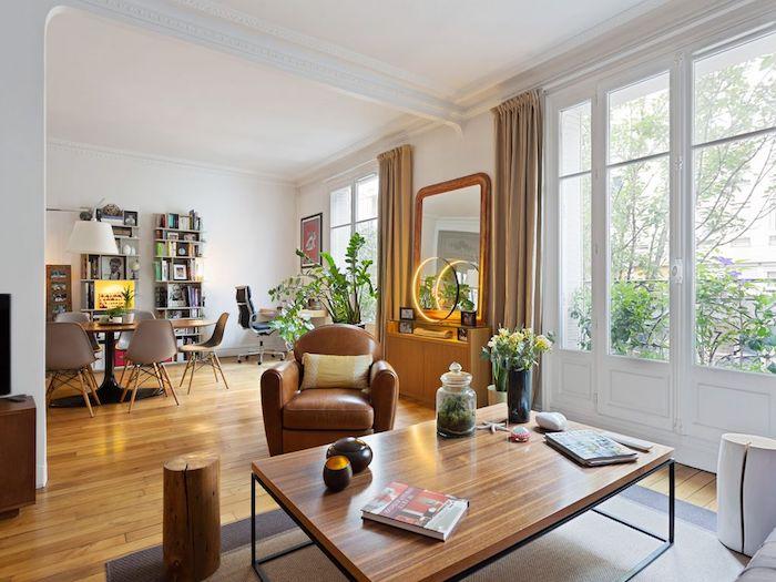 deco appartement haussmannien avec parquet bois clair mobilier bois et cuir étagères rangements livres salle à manger style scadninave