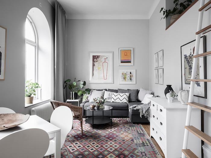 deco appartement parisien style scandinave avec canapé gris mobilier blanc tapis coloré géométrique rideaux gris plantes vertes