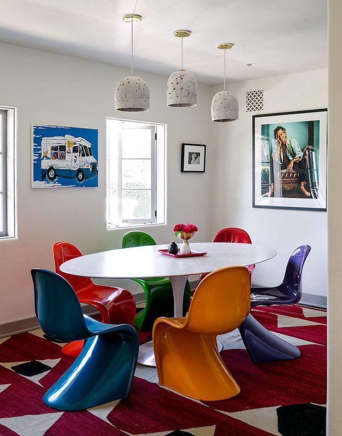 deco chaises dépareillées colroées autour d une table ovale de couleur blanche dans salon blanc avec tapis rouge et gris et art inspiration theme annee 70