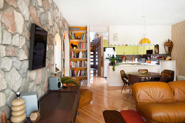 deco cuisine ouverte sur salon avec ilot central blanc credence noir et blanc meuble haut jaune suspension jaune parquet bois clair canapé fauteuil cuir marron meubles bois foncé wengé vintage