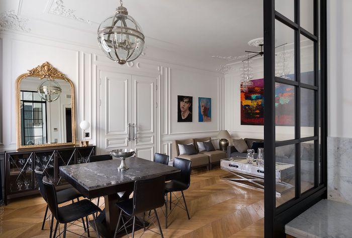 deco haussmannien avec table et chaises noires canapé gris et table coffret inox parquet bois clair murs blancs décorés de peinture art contemporain