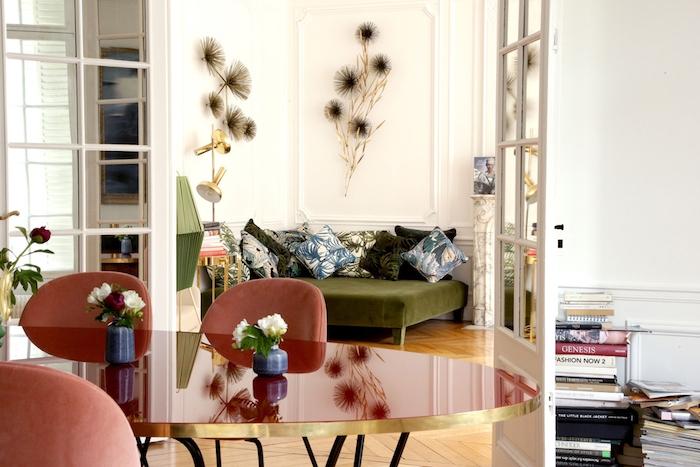 deco murale de fleurs canapé vert olive table et chaises salle à manger rouges parquet chevron clair piles de livres