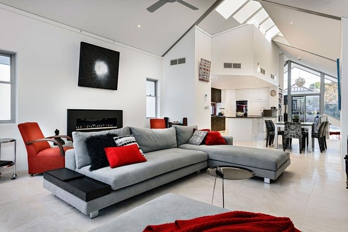 deco noir et blanc design salon sous pente fenêtre de plafond ventilateur coussin rouge canapé gris clair petite cuisine ouverte blanche