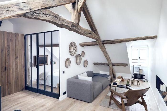 deco petit appartement salon sous pente avec canapé gris déco murale assiettes fauteuil de bois parquet bois clair verrière industrielle linge de lit blanc poutres apparentes style rustique