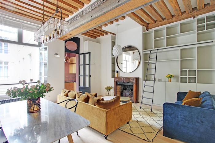 deco petit appartement studio abec canapé jaune et canapé bleu table marbre et bois meuble salon gris clair miroir rond au dessus de cheminée