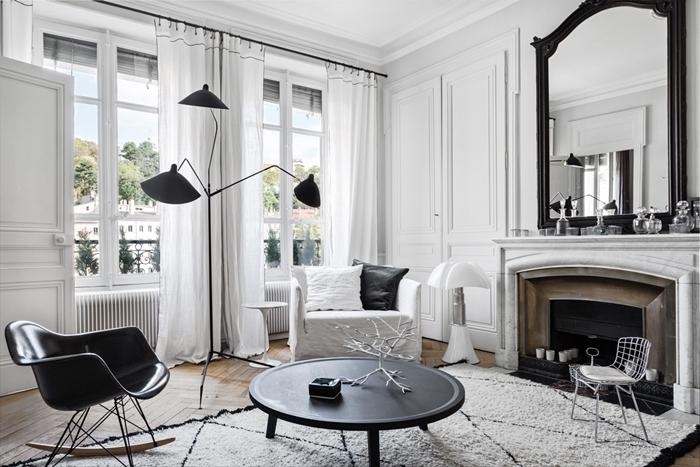 deco salon noir et blanc lampe sur pied noire miroir noir cheminée décorative bougie chaise blanche métal table basse ronde noire